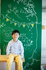 絵の書いてあるボードの前に座る男の子