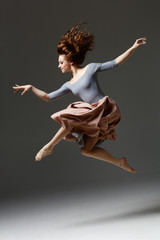 the modern dancer jumping on a gray background