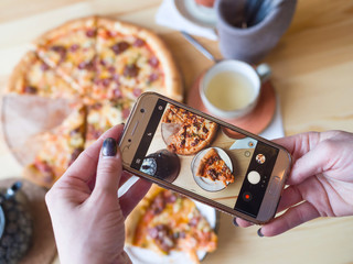 A woman takes a photo of a pizza on a smartphone for social networks.