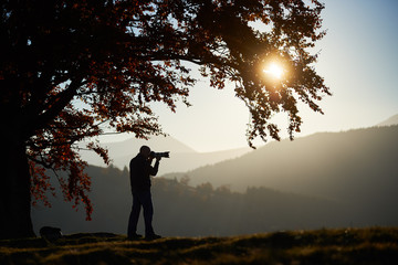 Hiker tourist man taking picture of beautiful mountain panorama at dusk and setting sun using camera standing under big tree with golden leaves on grassy valley. Tourism and photography concept.