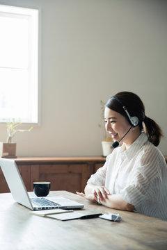 パソコンでテレビ電話を楽しむ20代女性の横顔