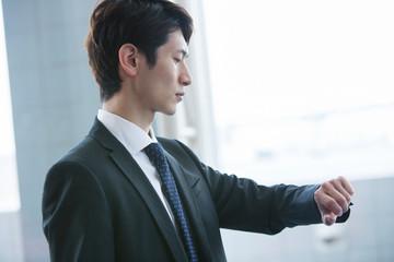 腕時計を確認するスーツ姿の20代男性