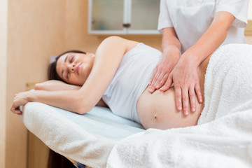 A beautiful pregnant brunette with long hair lies on her side at a reception with a massage therapist in a cosmetology room