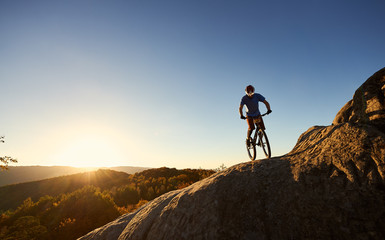 Silhouette of male cyclist riding on trial bicycle on top of big boulder, bicyclist making acrobatic trick in the evening, blue sky and sunset on background. Concept of extreme sport active lifestyle