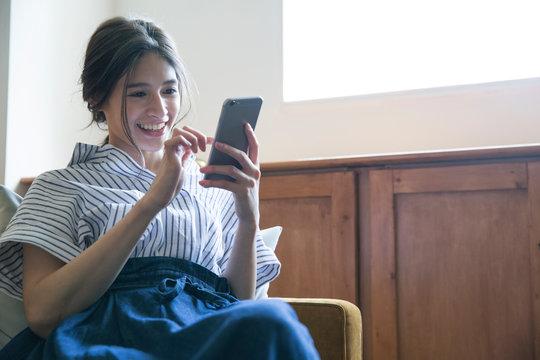 部屋でスマホを操作する笑顔の20代女性