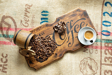 Scattered coffee beans, a cup of espresso, pieces of chocolate with nuts on a wooden board.