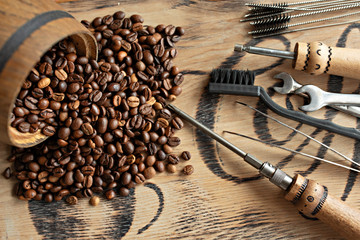Tools for repairing coffee machines close-up. Coffee beans, wooden board, coffee machine, kitchen...