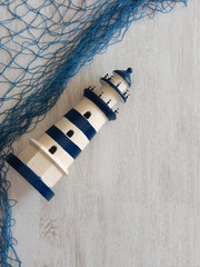 Toy lighthouses nautical blue decorative mesh on a wooden background
