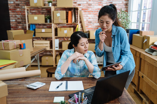 business coworkers woman fighting happy to online shopping working with laptop and box package in home office. real moment young girls employees in warehouse. two colleagues having discussion on pad