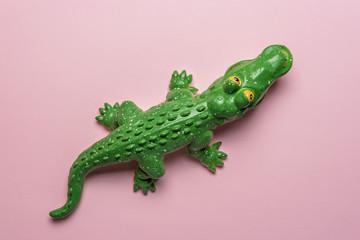 Green crocodile toy on pastel pink background. Minimal art concept.