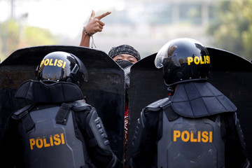 A protester gestures as mobile brigade (Brimob) police officers stand guard at a barricade during a protest near the Election Supervisory Agency (Bawaslu) headquarters in Jakarta