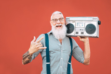 Fototapeta Happy senior man listening to music with boombox outdoor - Crazy hipster male having fun dancing with vintage stereo - Concept of elderly people lifestyle