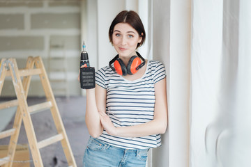 Wry young woman holding a power drill