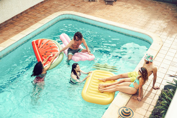 Happy friends having fun in swimming pool  during summer vacation - Young people relaxing and...