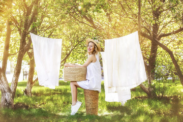 Beautiful young and happy woman hanging clean Laundry in the garden