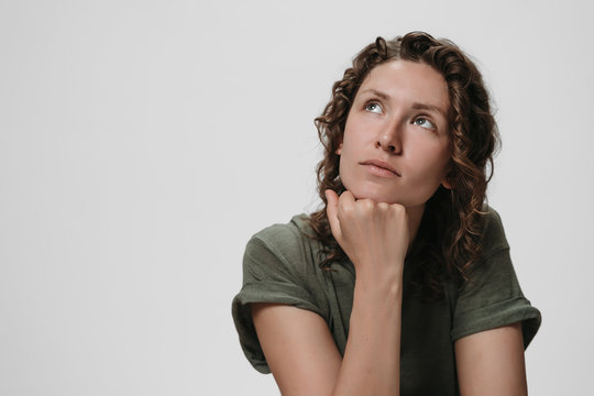 Young curly caucasian woman keeps hand under chin, being deep in thoughts