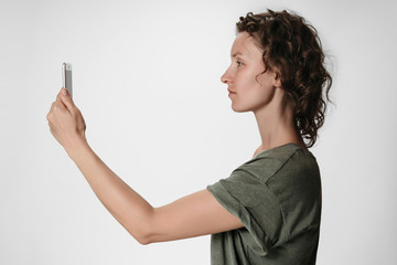 Young curly hair woman using smartphone face recognition isolated on white background.