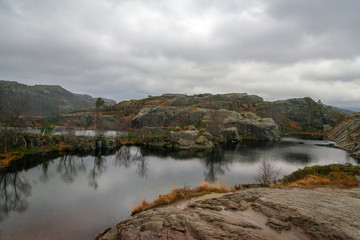 Gloomy, foggy day in Preikestolen, Norway. Beautiful landscape of rocky mountains and lake