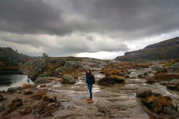 Brunette woman traveler hiking in rocky mountains in Preikestolen, Norway on cloudy day. Beautiful landscape.