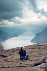 Tourist woman sitting on the edge of the cliff against foggy landscape of rocky mountains and fjord in Preikestolen, Stavanger, Norway. Top view