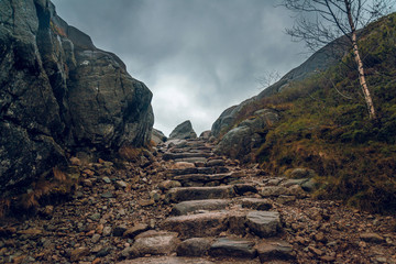 Stony path through the cliffs. Stony hiking trail in the mountains. Fotobehang
