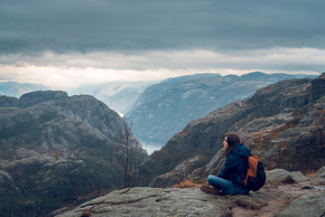 Woman sitting on the edge of the cliff and admiring beautiful landscape of rocky mountains and fjord in Preikestolen, Stavanger, Norway. Top view