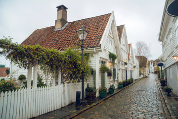 Beautiful street with traditional white wooden houses in Stavanger, Norway. Summer