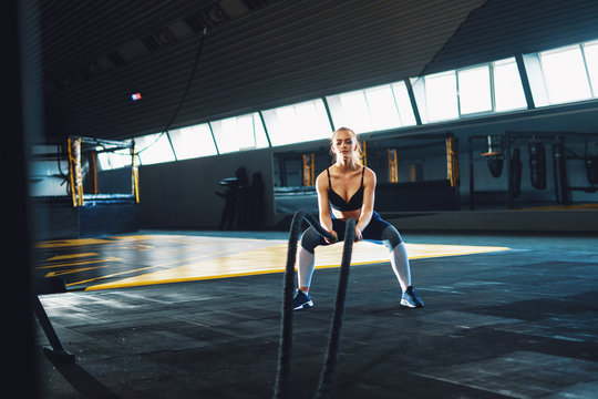 Full length wide angle shot of a young woman working out with battle ropes.  Copyspace background with athletics healthy composition. Crossfit and fitness