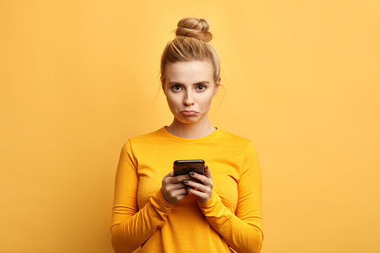 angry sad woman with hairbun annoyed by something while using phone, girl has received bad sms, text message isolated yellow background. emotion, reaction, feeling
