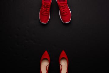 A studio shot of pair of running vs high heel shoes on black background. Flat lay. Fototapete