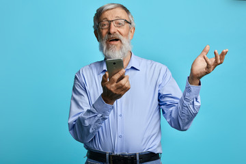 Old man raised hand holding mobile phone, making phone call, senior man uses gadget witjot problems. isolated light, sky blue background. man browsing net, surfing net, watching video. blogger concept