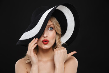Young shocked blonde woman with bright makeup red lips posing isolated over black wall background wearing hat.