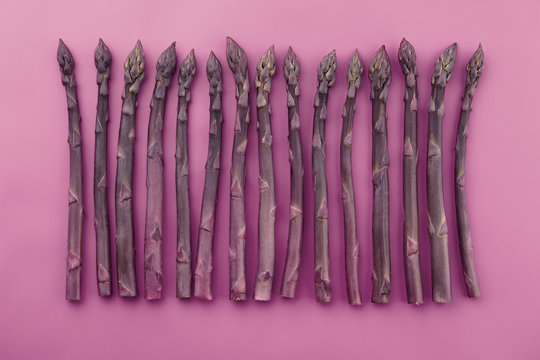 Fresh purple asparagus on violet background, top view