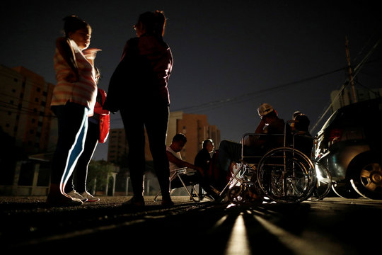 Patients with kidney disease and their relatives wait on the street for the return of electricity, in front of a dialysis center, during a blackout in Maracaibo