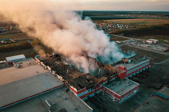 Aerial view of demolished burning industrial building by fire, huge smoke from broken roof, walls and piles of garbage