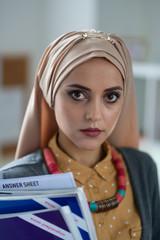 Dark-eyed Muslim teacher holding books standing in school
