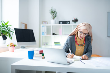 Young Muslim teacher sitting near laptop and writing notes