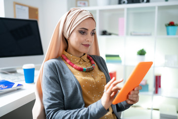 Beautiful Muslim woman with nice makeup using her orange tablet