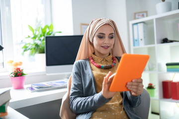 Appealing Muslim woman reading e-book feeling joyful