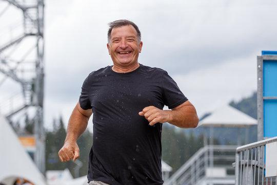 Smiling senior man running towards camera in rainy weather