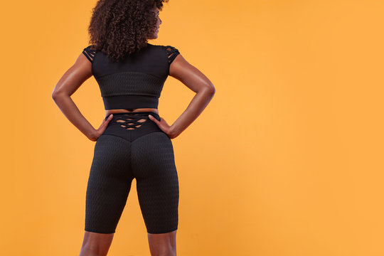 Back of strong athletic woman with black skin and curly hair, doing exercise on white background wearing sportswear. Fitness and sport motivation.