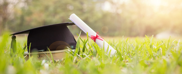 Closeup certificate paper and black cap on green grass spring time in the outdoor park. Education happy success achievement graduated celebrate graduate day concept panoramic background banner