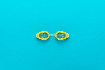 flat lay shot of yellow swimming goggles over turquoise blue background. minimalist photo of swimming goggles with central composition