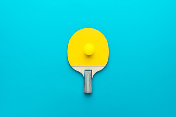racket and ball for table tennis on turquoise blue background. flat lay image of table tennis paddle with a ball central composition. minimalist photo of yellow ping-pong equipment