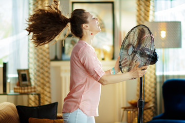smiling housewife enjoying fresh air in front of working fan