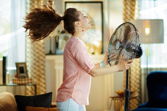 smiling housewife enjoying fresh air in front of working fan