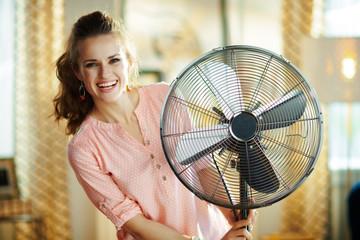 happy modern woman near electric floor standing fan
