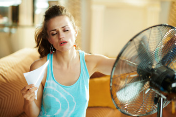 hot woman in front of working fan suffering from summer heat