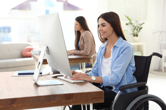 Young woman in wheelchair using computer at workplace