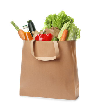 Paper bag with vegetables and bottle of juice on white background